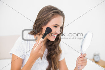 Smiling attractive brunette using a brush and a mirror