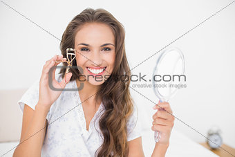 Smiling attractive brunette holding an eyelash curler and mirror