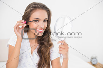 Smiling attractive brunette applying mascara and holding mirror