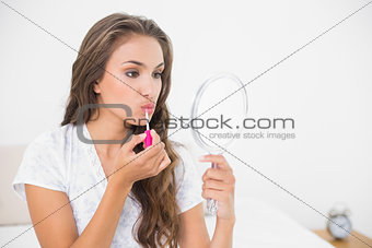 Serious attractive brunette applying lip gloss and holding mirror