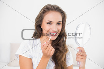Smiling attractive brunette applying lip gloss and holding mirror