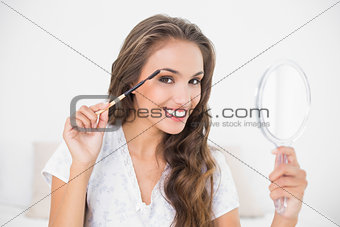 Smiling attractive brunette using eyebrow brush and mirror