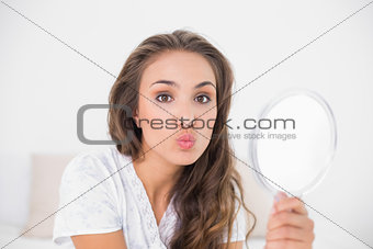 Posing attractive brunette holding mirror