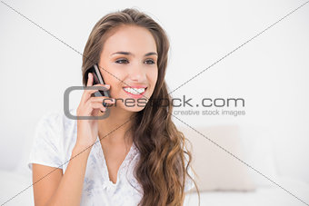 Smiling attractive brunette holding mobile phone
