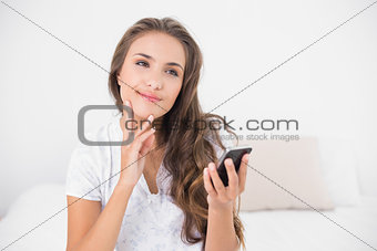 Thoughtful smiling brunette holding smartphone