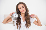 Tired brunette holding alarm clock