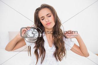 Tired brunette holding alarm clock