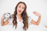 Yawning brunette holding alarm clock