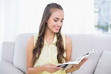 Smiling pretty brunette reading magazine