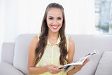 Smiling pretty brunette holding magazine