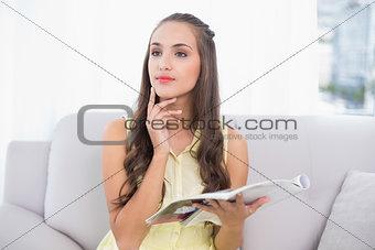 Thoughtful pretty brunette holding magazine