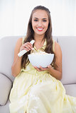 Smiling pretty brunette holding remote and popcorn