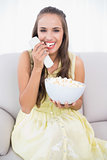 Laughing young brunette eating popcorn
