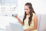 Smiling young brunette using credit card and laptop