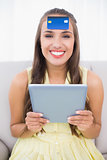 Happy brunette with credit card on forehead holding tablet