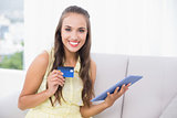 Smiling young brunette holding credit card and tablet