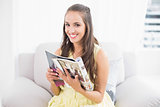 Happy young brunette holding magazine