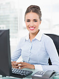 Smiling young businesswoman sitting in front of computer