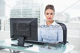 Calm brunette businesswoman sitting at her desk