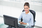 Smiling brunette businesswoman sitting at her desk