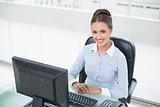 Smiling brunette businesswoman sitting at her desk