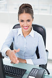 Smiling brunette businesswoman shaking hands