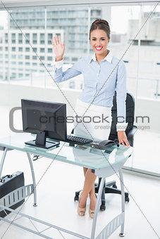 Smiling brunette businesswoman waving