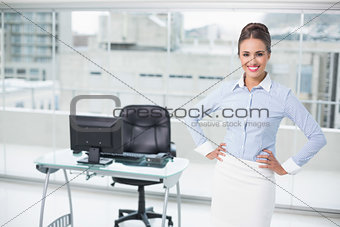Smiling brunette businesswoman standing hands on hips