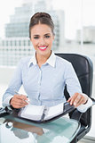 Smiling brunette businesswoman holding a diary