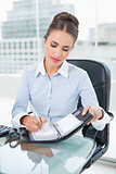 Content brunette businesswoman writing in a diary