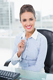 Smiling brunette businesswoman holding a pen