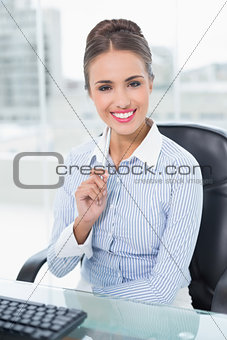 Smiling brunette businesswoman holding a pen