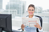 Smiling brunette businesswoman holding documents