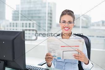 Smiling brunette businesswoman holding documents