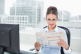 Content brunette businesswoman holding documents