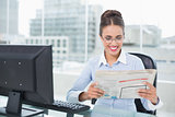 Happy brunette businesswoman holding documents