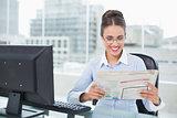 Happy brunette businesswoman holding documents
