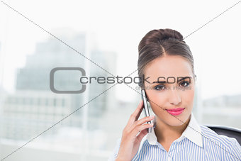 Smiling brunette businesswoman phoning with smartphone