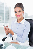 Smiling brunette businesswoman touching smartphone