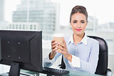 Content brunette businesswoman holding disposable cup
