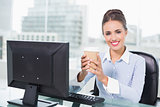 Smiling brunette businesswoman holding disposable cup
