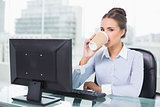 Calm brunette businesswoman drinking from disposable cup