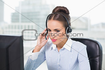 Calm brunette businesswoman using headset