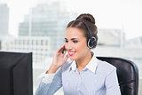 Smiling brunette businesswoman using headset