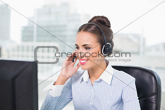 Smiling brunette businesswoman using headset