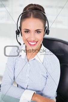 Smiling brunette businesswoman wearing a headset