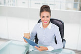 Smiling businesswoman holding tablet and disposable cup