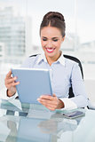 Happy brunette businesswoman using tablet
