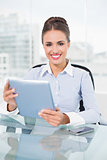 Happy brunette businesswoman holding tablet