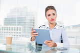Serious brunette businesswoman holding tablet